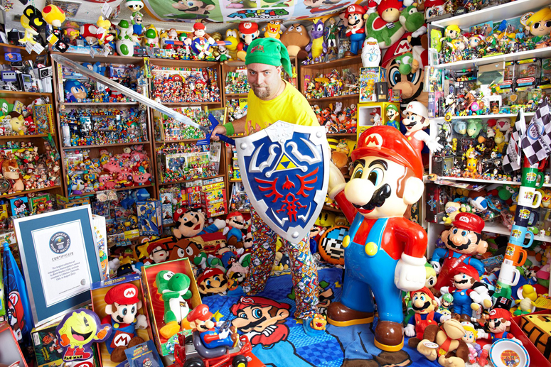 "Embargo:  00.01am on Thursday 10th January 2013 Photographer Credit:  James Ellerker/Guinness World Records Photo Caption: 31-year-old Brett Martin from Colorado, USA, is recognised in the new Guinness World Records 2013 Gamer's Edition for having the world's Largest Collection of Videogame Memorabilia, with 8,030 items of merchandise.  Brett, a web designer, was given his first item (a Mario figurine) by his parents when he was just 8 years-old; however he only started collecting 12 years ago when he ""discovered eBay"".  In that period he has amassed a collection worth in excess of $100k.  Brett, who is married with children, says: ""Many of my friends know I'm a gamer, but I guess after this they'll realise just how passionate and obsessed I am!"" Press Release: Guinness World Records™ Reveal Extraordinary New Gaming Feats in Guinness World Records 2013 Gamer's Edition LONDON (10/01/2013). Guinness World Records, the global authority on record-breaking achievement, reveal the latest and greatest gaming achievements in the new Guinness World Records 2013 Gamer's Edition out today.  Incredible new feats recognised in the best-selling videogame series include the Largest Collection of Videogame Memorabilia; Highest Margin of Victory against the Computer on FIFA; Highest Earning Call of Duty Player; and the Smallest Arcade Machine. 31-year-old Brett Martin from Colorado, USA, is recognised in the new Guinness World Records 2013 Gamer's Edition for having the world's Largest Collection of Videogame Memorabilia, with 8,030 items of merchandise.  Brett, a web designer, was given his first item (a Mario figurine) by his parents when he was just 8 years-old; however he only started collecting 12 years ago when he ""discovered eBay"".  In that period he has amassed a collection worth in excess of $100k.  Brett, who is married with children, says: ""Many of my friends know I'"